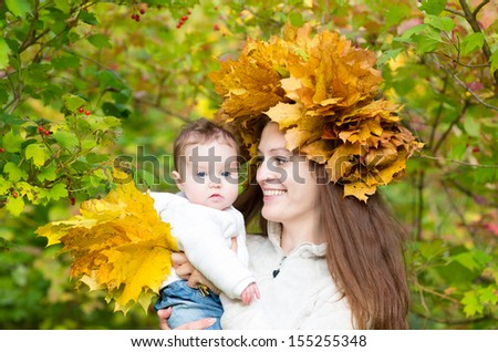 Young attractive mother in a maple leaf wreath holding a sweet baby girl in a beautiful autumn park - stock photo