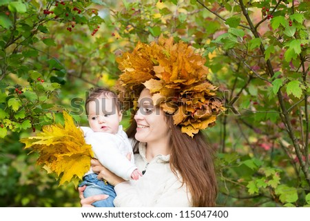 Young attractive mother in a maple leaf wreath holding a sweet baby girl in an autumn park - stock photo