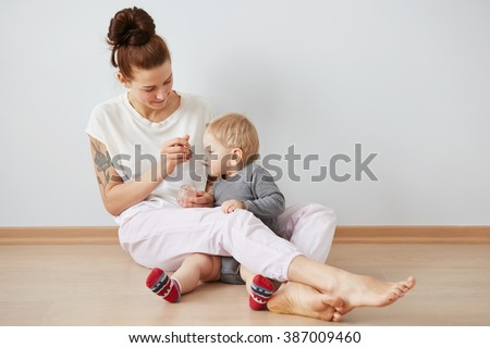 Young attractive mother with her one years old little son dressed in pajamas  giving him his first fruit smoothies food in the bedroom at the weekend together, lazy morning. Selective focus