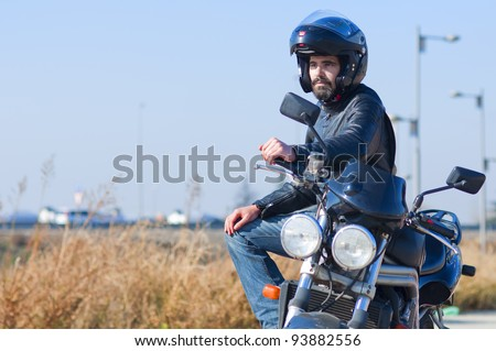 Young attractive motorcycle resting in the way - stock photo
