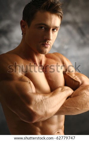 Young attractive muscleman poses - stock photo