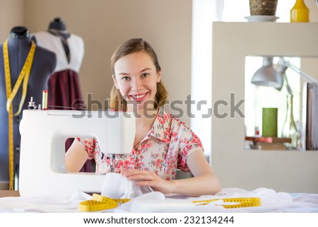 Young attractive needlewoman at studio working with sewing machine