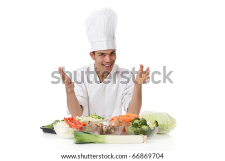 Young attractive nepalese man chef presenting variety of fresh vegetables. Ingredients for oriental food. Studio shot, white background. - stock photo