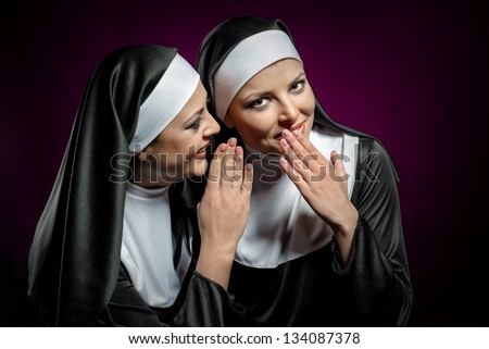 Young attractive nun whispering a secret to another nun - stock photo