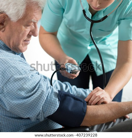Young attractive nurse checking the elderly man's hypertension - stock photo