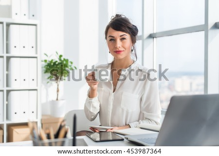 Young attractive office worker drinking cup of tea, having coffee break in the morning, getting ready for work day - stock photo
