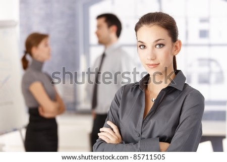 Young attractive office worker standing arms crossed in office, young businesspeople chatting in the background.?
