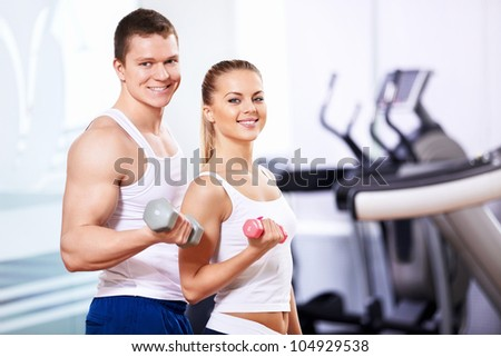 Young attractive people with dumbbells - stock photo