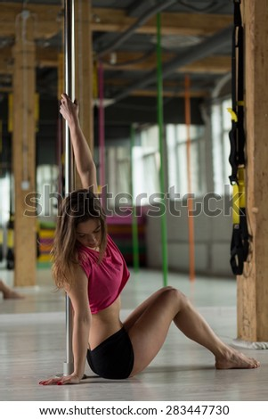 Young attractive pole dancer training before show - stock photo