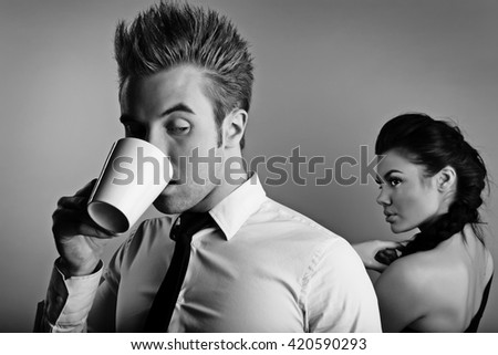 Young attractive & positive couple posing on studio background. Black-white photo.