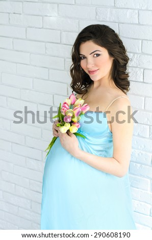 young attractive pregnant woman in aqua decollete gown with bouquet of yellow and pink tulips on white brick wall background