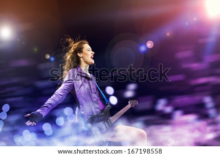 Young attractive rock girl playing the electric guitar