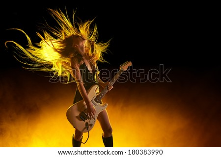 Young attractive rock girl playing the electric guitar - stock photo