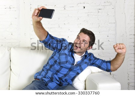 young attractive 30s man taking selfie photo or self video with mobile phone at home sitting on couch smiling happy in use of technology and image concept - stock photo
