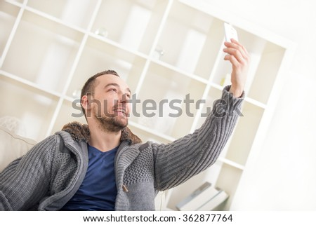 Young attractive 30s man taking selfie picture or self video with mobile phone at home - stock photo