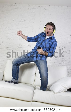 young attractive 20s or 30s man having fun jumped on home couch listening to music on mobile phone with headphones dancing , singing and playing air guitar happy and crazy - stock photo