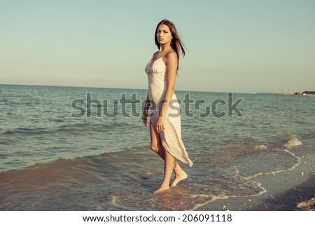 Young attractive sad girl near the sea on a summer day