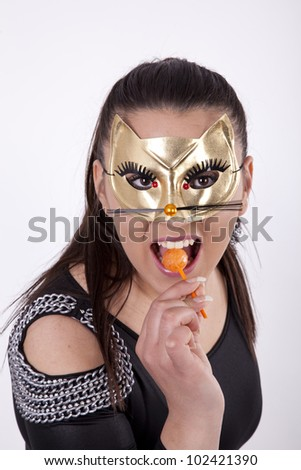 Young attractive sexy masked like cat woman licking lollipop.