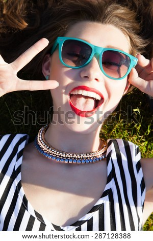 Young attractive sexy woman laying on the ground,wear summer outfit of striped dress,swag sunglasses,daily make up with red lips.Laughing and show peace sign.Look at camera and smiling.bright selfie - stock photo