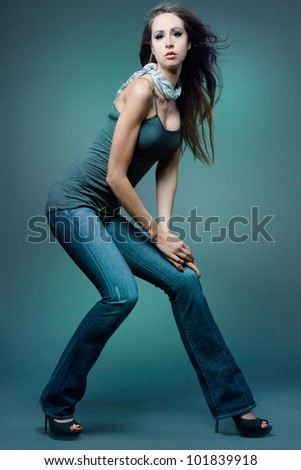 Young attractive slim fashion model posing on dark background.