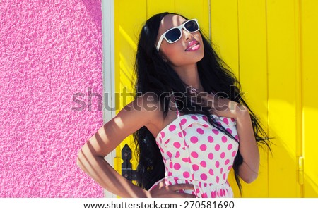 Young attractive smiling african american woman wearing sunglasses - stock photo