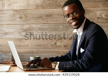 Young attractive smiling African male, typing a message via social networks on laptop, sitting at a restaurant, looking formal in his jacket, watches and glasses, isolated against wooden background - stock photo
