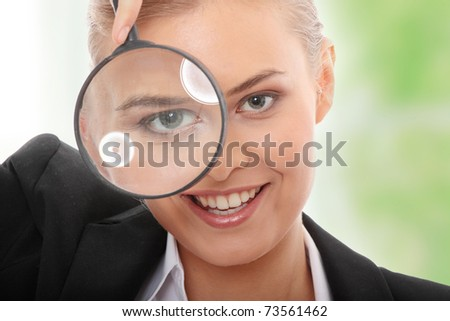 Young attractive smiling business woman looking into a magnifying glass.
