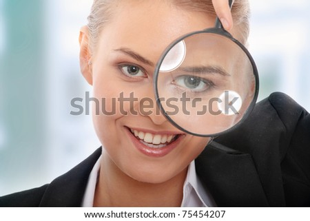 Young attractive smiling business woman looking into a magnifying glass, isolated on white background - stock photo