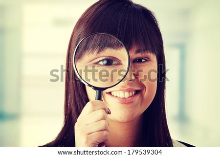 Young attractive smiling business woman looking into a magniying glass  - stock photo