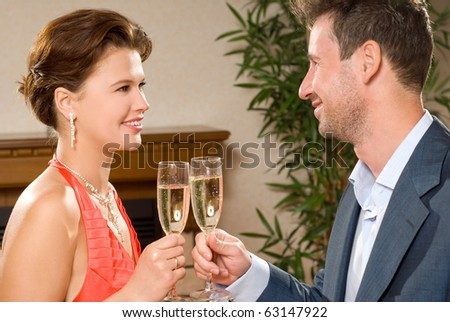 Young, attractive, smiling couple celebrating with champagne, indoors