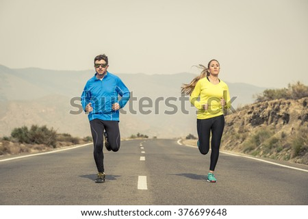 young attractive sport couple of man and woman running together on asphalt road with mountain landscape background looking happy and healthy in team training workout , fitness and wellness concept - stock photo