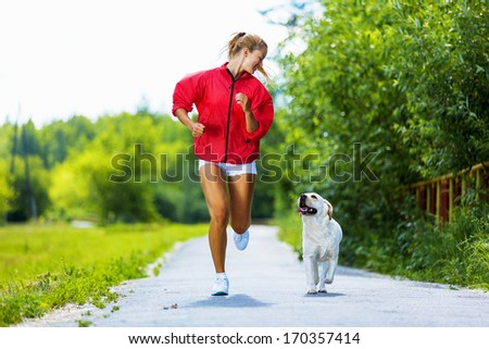Young attractive sport girl running with dog in park - stock photo