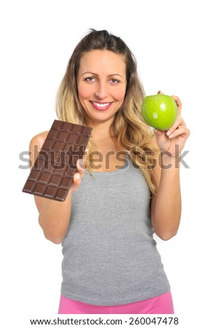 young attractive sport woman holding apple and chocolate bar in her hands in healthy fruit versus sweet junk food temptation in fitness, body health care and healthy nutrition concept - stock photo