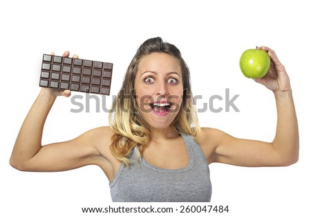young attractive sport woman holding apple and chocolate bar in her hands in healthy fruit versus sweet junk food dilemma in fitness, body health care and healthy nutrition concept - stock photo