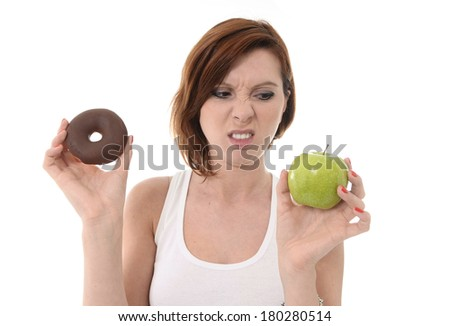 Young attractive sport Woman holding Apple and Chocolate Donut in Hands in healthy versus junk food dessert choice isolated on White background - stock photo