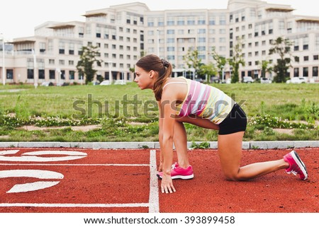 Young attractive sporty girl in sportswear in steady position on start of running track on university campus stadium preparing to run. Standing in half-steady position on knee - stock photo