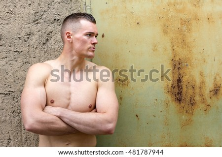 Young, attractive, sporty man leaning against a wall / young man / sportsman