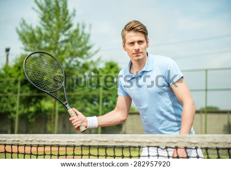 Young attractive sporty man play tennis outdoors in the morning. - stock photo