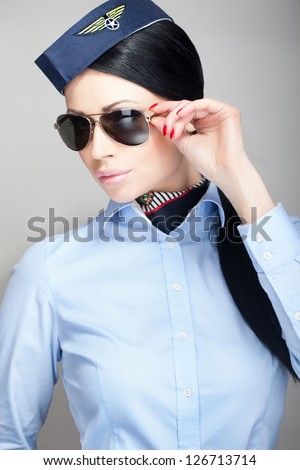 Young attractive stewardess flight attendant with aviator sunglasses - stock photo