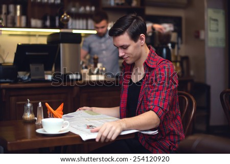 Young attractive student drinking coffee and reading newspaper in the cafe with barista on the backside. - stock photo