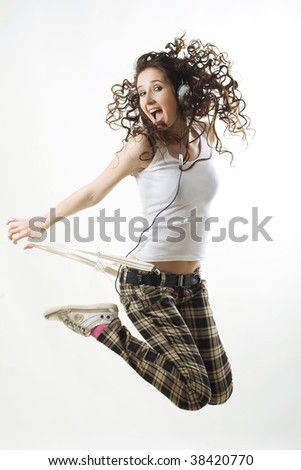 Young attractive student jumping in the air whilst listening to music through headphones.