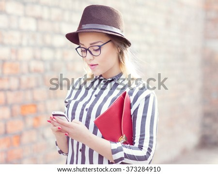 Young attractive student woman wearing hat and glasses holding a briefcase using a smart phone in the street. Technology internet communication and social media concept. - stock photo