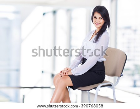 Young, attractive, successful business woman, sitting on a chair. - stock photo