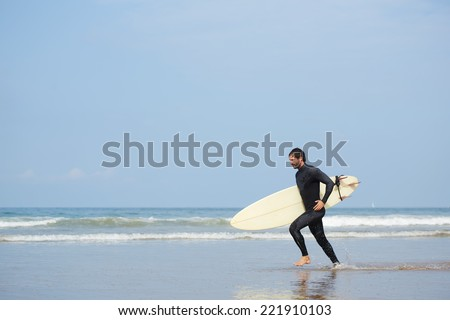 Young attractive surfer runs with surfboard along the shore, cold season surfing at ocean beach, professional surfer man dressed in wetsuit ready to surfing runs to the waves
