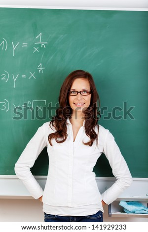 Young attractive teacher with brown hair smiling at the camera against a green board.