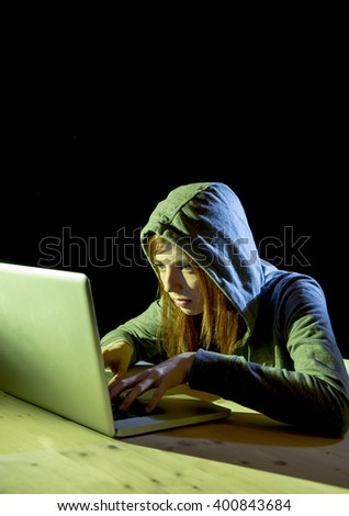 young attractive teen woman wearing hood on looking dark and dangerous hacking laptop computer system on black background in cybercrime or cyber crime and internet criminal concept  - stock photo