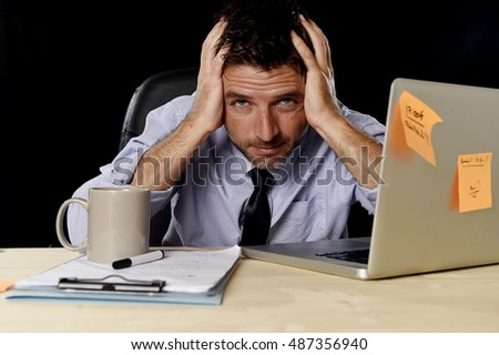 young attractive tired businessman in shirt and tie tired and overwhelmed by heavy work load exhausted at office desk with laptop computer in business stress overwork and overtime concept