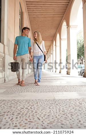 Young attractive tourist couple shopping and walking together holding hands while visiting a destination city on holiday. Joyful boyfriend and girlfriend in a classic architecture city relaxing. - stock photo