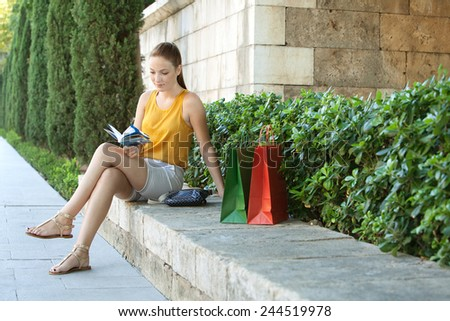 Young attractive tourist woman sitting and relaxing on a stone bench in a green park with sightseeing activities, reading a travel guide book with shopping bags. Travel and lifestyle outdoors.
