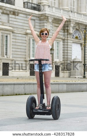 young attractive tourist woman with red hair wearing shorts and summer singlet riding happy electrical segway having fun driving free hand in touristic city tour in Madrid royal palace in Spain - stock photo